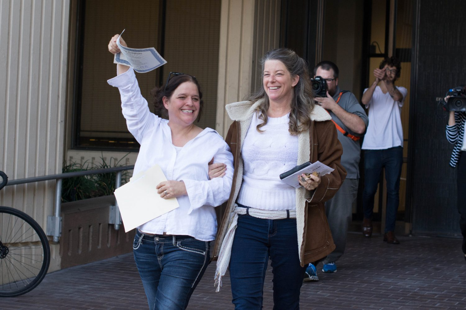 Joy Drawdy (left) holds up her new marriage license with Kat Drawdy (right) exit the Alachua County Courthouse with m