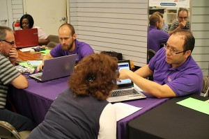 Navigators James Old, left, and Juan Genao-Homs, with the Epilepsy Foundation of Florida, explain the health coverage options to consumers at an enrollment event in Jacksonville, Fla.