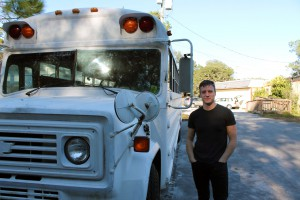 Davis Hart stands next to one of his busses, which he said can comfortably fit seven.  The bus, which runs on vegetable oil, has held up to 16 and has compartments built in to hold instruments and tools.