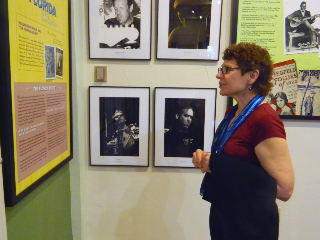 Gainseville resident Mary Mills reads caption that corresponds to the collage of famous blues photos at the Matheson History Museum Sunday.