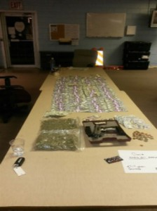 Marijuana, cash, a 9mm semi-automatic handgun and other evidence seized from Guion's truck lies on a table. A KN Reagent marijuana test kit confirmed the bagged substance was marijuana.