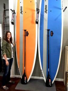 Kate Maurer stands next to two of the fiberglass paddleboards she's going to start selling and renting next month. Maurer and her fiancé are opening a paddleboard shop and an antique shop in The Corner next month.