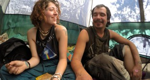May Bear laughs with Earl while giving him a stick-and-poke tattoo in their tent in the Ocala National Forest on Jan. 24. They were among the first people of the Rainbow Family to help built the site for the  Rainbow Gathering.