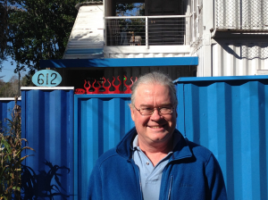Tom Fox, 51, stands in front of his blue fence door that allows him access to his one-of-a-kind home. The first floor of his house houses his garage and his workshop.