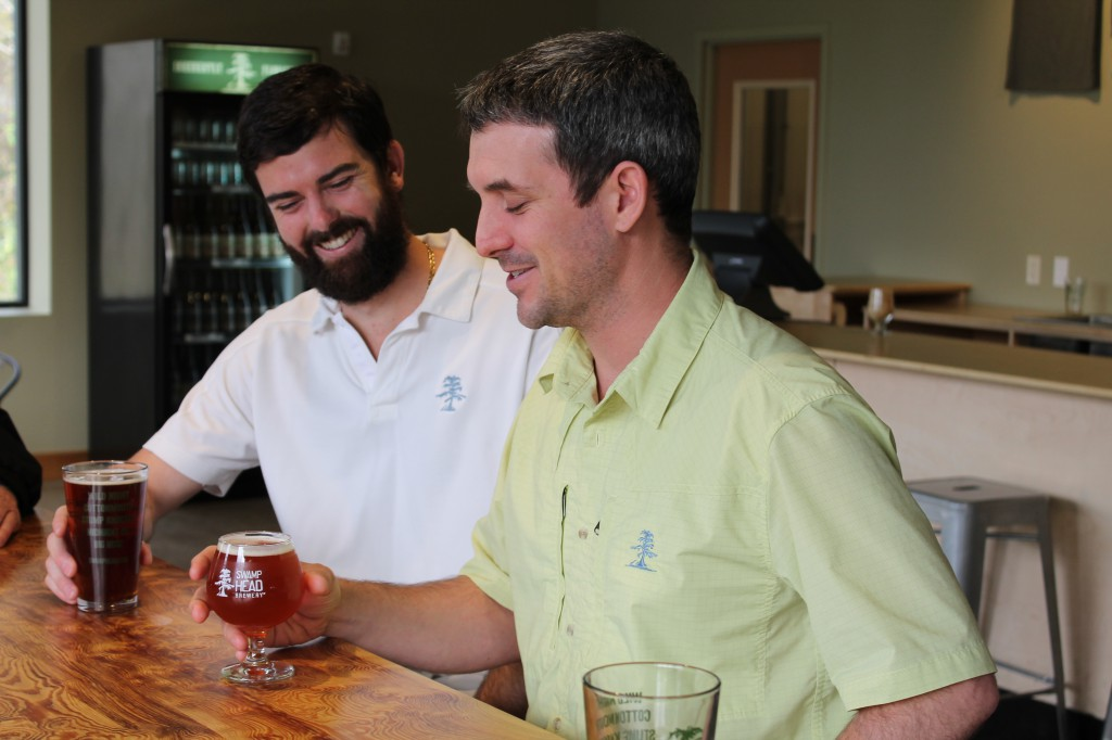 Luke Kemper, the owner of Swamp Head Brewery, shares a laugh over a beer with tactical manager Brandon Nappy. The brewery creates many seasonable beers but has found success from the first original five beers, which are available year round.