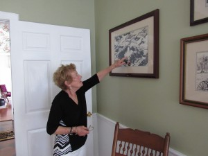 Suzanne Thomas points out aerial photos of downtown Ocala hanging in the front parlor of the W.R. Bryant house located on the historic East Fort King Street.