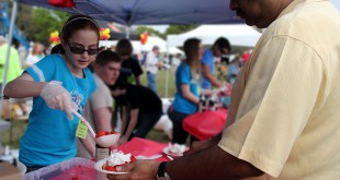 Kayla Gilligan, 11, serves strawberry shortcakes at the second annual Strawberry Festival in Ocala. Gilligan, who attends Howard Middle School, says volunteering for Habitat for Humanity is fun, knowing that it helps toward making a difference in the community she lives.