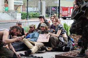 A group of 'dirty kids' fly a sign on the corner of SE 1st St and SE 2nd Pl while one patches up a jacket and another plays guitar on Jan. 23, 2015 in Gainesville. Photo by Andrea Sarcos/WUFT News