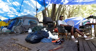 David Cleveland sits outside his tent in Dignity Village near Grace Marketplace Tuesday, March 10, 2015. Cleveland's campsite is located on a 10 acre span of land that the city of Gainesville will lease from the state.