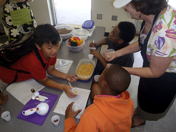 Students at Stephen Foster Elementary School learn the basics of nutrition education from retired University of Florida dietetics professor Dr. Pam McMahon. Kids in the Kitchen is a county wide program sponsored by the Department of Children and Families, UF and the USDA. Photo courtesy of Bailey Bruce / Foster Elementary Afterschool Coordinator.