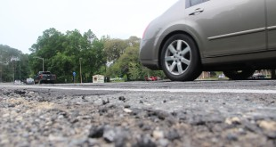 Cars drive past the filled-in potholes and cracks. Permanent road repairs are not expected until after July 2016. Ronnie Socash / WUFT News