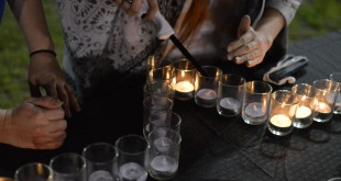 A staff member encourages a speaker to light a candle after telling her story of domestic abuse to Take Back the Night attendees. The candles were lit to remember those who were affected by sexual violence.