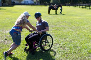 HOrses Helping PEople co-founder and occupational therapist Cathi Brown pushes Lauren Ault toward a wheelchair ramp prior to her hippotherapy session at the HOPE farm in Archer on April 8.