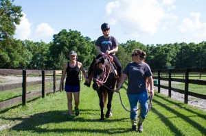 HOrses Helping PEople intern Mallory Johnson (left) and barn manager Kaylie Madore (front) walk with Lauren Ault while she rides Lila during a hippotherapy session at the HOPE farm in Archer on April 8.