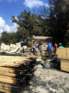 J.L. Wood Gator Reman sawmill employees work to remove debris after a shed caught on fire Wednesday morning. They hope to be fully operational by Friday, said owner John Whitehead. Abbie Banitt / WUFT News