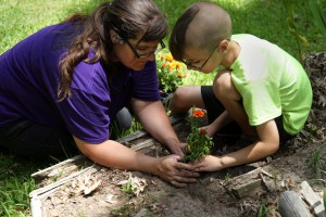 Kelly Johnson and her 8-year-old son, Aiden, plant marigolds. The entire family is part of the therapy at 10 CAN because the founder, Matthew Burke, believes that if you help the family of the veteran, you end up helping the veteran too.