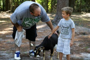 Jeremy Johnson coaxes 6-year-old River Nico into petting one of the goats at 10 CAN Farm. Nico's father, Richard Nico, was the winner of the 10 CAN Survival Race and donated his winnings back to the organization because he believes in its mission.