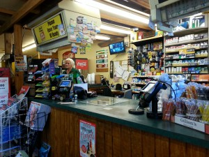 Donni Young works behind the counter at Pearl Country Store and Barbecue. She said this summer is the best the Micanopy convenience store and restaurant has seen in her three years as manager of it. Photo by Nicole Gomez