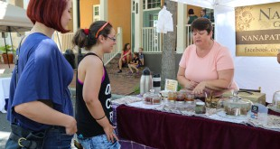 Pat McCarthy, owner of Nana Pat's Goodies, talks to Dallis Rossi and Stephanie Welches about the jam and mustard samples displayed on her stand at the Haile Farmers Market on Saturday morning.