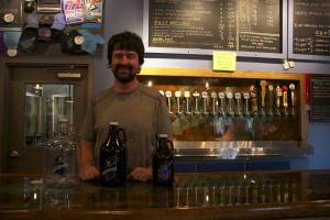 John Denny, the head brewer and a co-owner of First Magnitude Brewing Co., poses with the growlers the brewery sells. Starting July 1, breweries can legally sell the 64-ounce size in Florida. Nicole Gomez / WUFT News