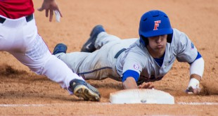Dalton Guthrie slides head-first back to first base.