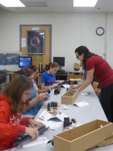 Graduate student Tahlia DeMaio helps girls in WiSE Girlz summer camp build a telescope.