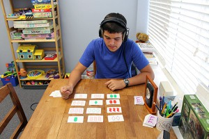 Nate Willingham focuses on matching three cards based on color, shape or pattern during his Brain Works session on Friday. This card game is used to improve visual perception.