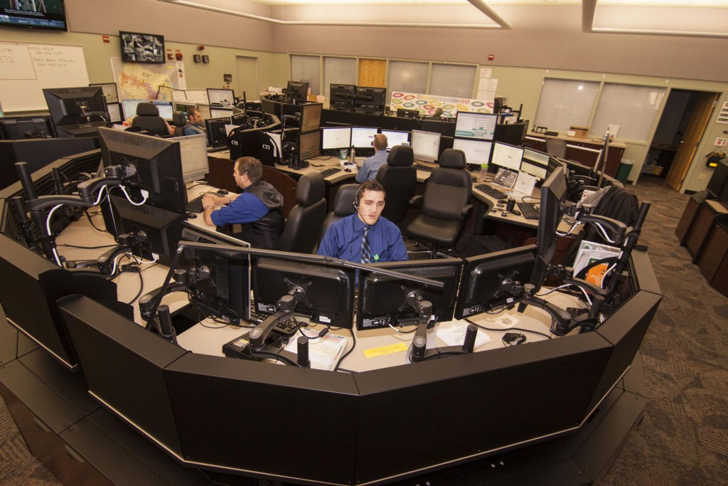 "Matthew Russell (left), emergency telecommunicator, inputs information into the dispatch system while his trainee Brian Ehemann (right) responds to a 911 call. ""Everyone in there wants nothing but the best for those on the phone,"" Russell said. ""Regardless of what they are calling in for."" Photo courtesy of Anthony Russell."