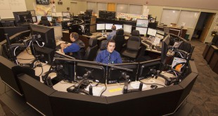 "Matthew Russell (left), emergency telecommunicator, inputs information into the dispatch system while his trainee Brian Ehemann (right) responds to a 911 call.  ""Everyone in there wants nothing but the best for those on the phone,"" Russell said. ""Regardless of what they are calling in for.""  (Photo courtesy of Anthony Russell)"