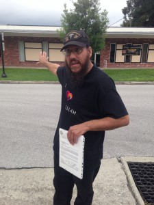 Chris Martin holds his Navy Discharge papers while standing outside Florida Gun Supply. The business cancelled it's week gun training class.