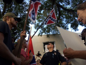 "An officer stands at the fault line between the two sides of the protest. Despite the cries of ""The South will rise,"" and counter-cries, ""We are the South,"" many of the protesters also tried to civilly discuss their differences over the statue of the Confederate soldier."