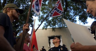 "This photo taken July 10 shows an officer stands at the fault line between the two sides of the protest. Despite the cries of ""The South will rise,"" and counter-cries, ""We are the South,"" many of the protesters also tried to civilly discuss their differences over the statue of the Confederate soldier."