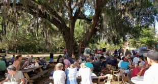 """About 200 street and church people eating and worshipping together at Church in the Garden, which is organized by Ken and Wendy Kebrdle. """"It is not us  putting on a worship service for poor folks,"""" Ken said. """"They are involved, they are  the band, they teach and they help with communion. It's us worshipping with them."""""""