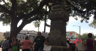 A protester adds his sign to the many others propped against the downtown statue of the Confederate soldier during Thursday night's rally. Those who want to keep the statue in its original downtown location brought Confederate flags, some dressing in period-appropriate clothing.