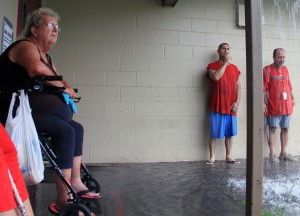 Amanda Norman and two other Grace Marketplace residents wait outside the kitchen doors as it rains heavily. Norman has lived in Dignity Village for more than two months. photo by Thomas Lynn