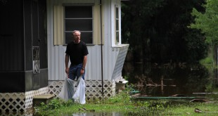 Flooding2: Ron Legler, 61-year-old Yankeetown Fla., resident, peers over his soaked yard. His house avoided significant water damage as it sat six to eight inches above the waterline. Susan Huang / WUFT News