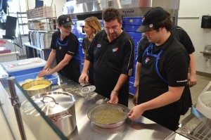From left to right: Domino's employees Geo Crume (far left) and Sawyer Cunningham (far right) make pizzas at the new pizza theatre store. The store on Archer is the first location to offer exclusively digital services.