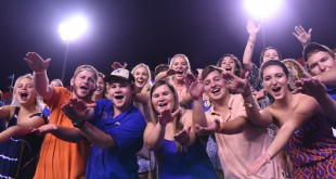 Florida fans showing their school spirit by doing the Gator chomp.
