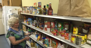 Evelyn McKoy checks her inventory of food stacked on shelves inside her shed. The food is placed in brown bags that feeds about 500 people every two weeks.