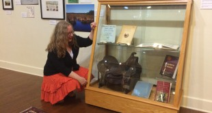 Executive director of the Matheson History Museum Peggy Macdonald admires artifacts of Marjorie Harris Carr. The zoologist used the leather saddle on research trips to Honduras in the 1940s.