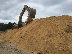 A construction truck piles up sandy soil on the perimeter of the project site. About eight inches of this is placed on the site first folowed by two feet of clean soil and sodding mats. Photo by Conor Soper.
