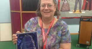 Librarian Gail Carr holds the library's NEFLIN Innovation of the Year award. NEFLIN presents the award to libraries that exhibit creativity in library programming
