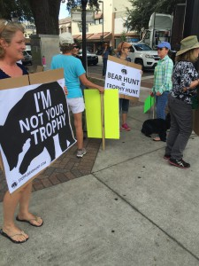 People hold signs at the intersection of University Avenue and Main Street, protesting the first legal bear hunt in state of Florida in 21 years.