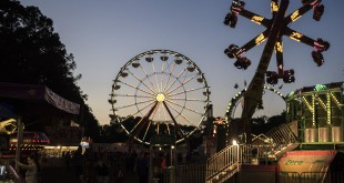 The sun sets behind the trees at the Alachua County Fairgrounds as fair-goers enjoy the Ferris Wheel and Power Surge rides. File/WUFT News
