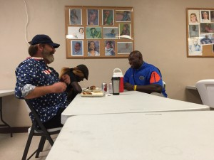 Thaddeus Bullard sits with homeless couple, Joe and Vivian Mulligan, as he listens to their story.