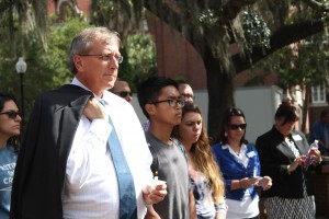 UF President Kent Fuchs holds a candle in memory of the victims of shootings on the campuses of UCC and NAU. He said it was a priority to be at the event with students.