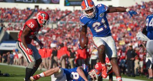 Florida running back Kelvin Taylor (21) leaps over teammate Jake McGee (83) to score a 3-yard touchdown in the second quarter. Taylor rushed for  two touchdowns, and 121-yards on 25 carries.