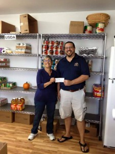 Joe Catalano hands a check from the proceeds of the Cedar Key Pirate Invasion to Cedar Key Food Pantry Treasurer Jeri Treat. Photo courtesy of Joe Catalano.