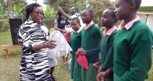Lucy Ragwa, the wife of governor Samuel Ragwa Mbae in Tharaka Nithi Kenya, hands out Days for Girls International Hygiene Kits to students. Photo submitted by