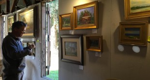 Charles Dickinson, one of the artists participating in the 2015 Evinston Plein Air Paintoff, hangs his work in the gallery next to the Wood and Swink General Store and Post Office where it will be available for purchase. Half of the money raised from his artwork will be put toward preserving the store.
